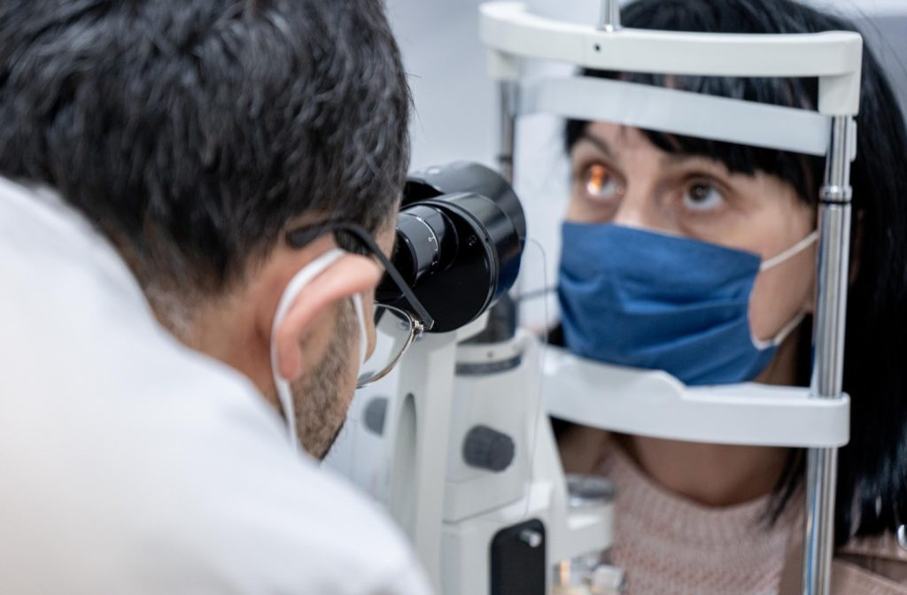 An optometrist conducting an eye examination while both wear face masks