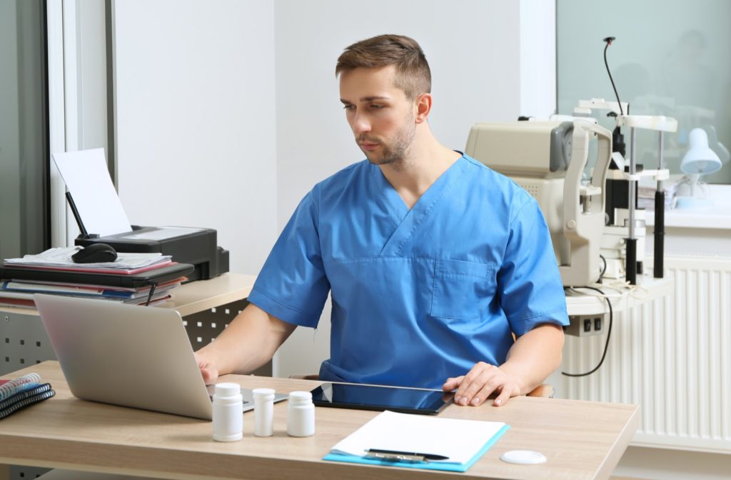 Optometrist using electronic medical records software in his office.