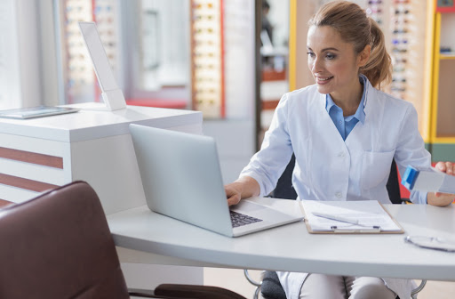 Optometrist smiling and using electronic medical records software at an optometry clinic.