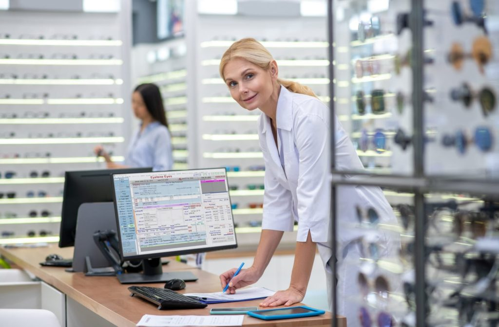 Happy optometrist looking at camera and working with Visual-Eyes software program as customer shop around.