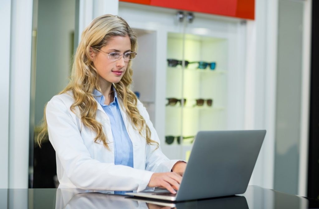 optometrist focusing on her work as she works on her laptop at her office